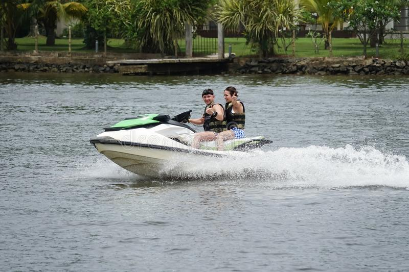 Happy young couple with thumbs up enjoying and having fun riding on a jet ski royalty free stock images