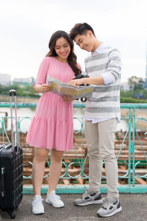 Happy young couple of travellers holding map in hands.  stock photos