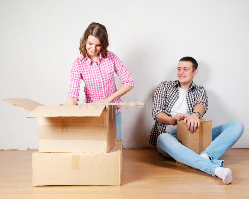Happy young couple unpacking or packing boxes and moving into a new home. stock photos