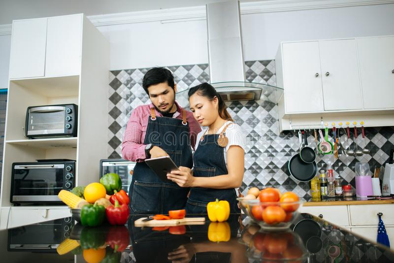 Happy young couple is using digital tablet to looking method to cooking while cooking in kitchen stock photo