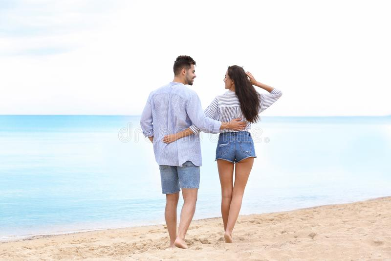 Happy young couple walking  on beach near sea royalty free stock photography