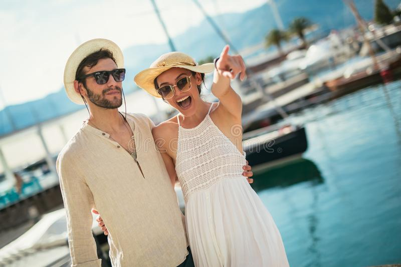 Happy young couple walking by the harbor of a touristic sea resort stock images