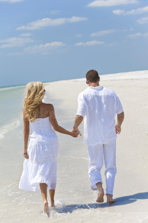 Happy Young Couple Walking Holding Hands on Beach stock photo