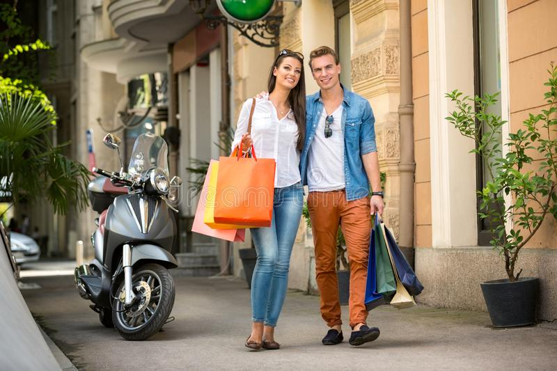 Couple walking leisurely together with shopping bags stock photo