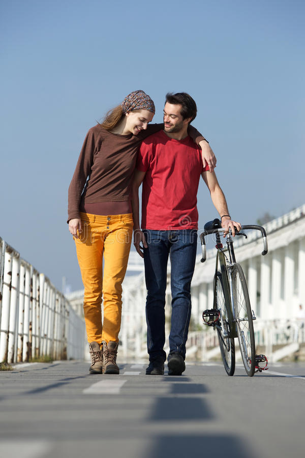 Happy young couple walking outdoors with bike stock photos