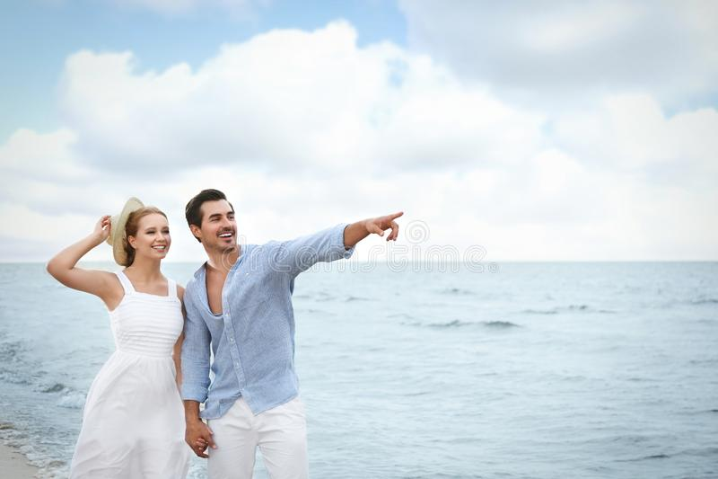 Happy young couple  on sea beach stock photos