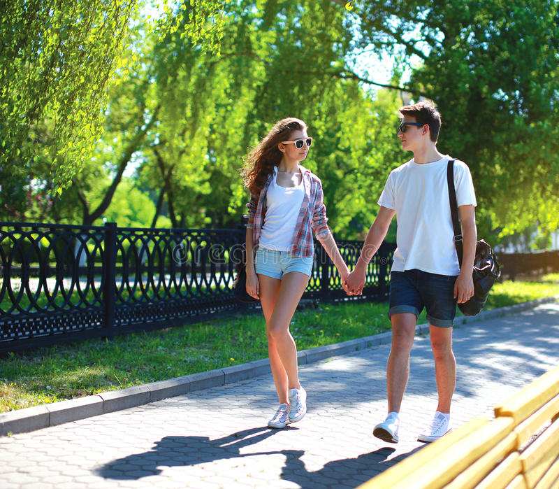 Happy young couple walking in summer park royalty free stock images