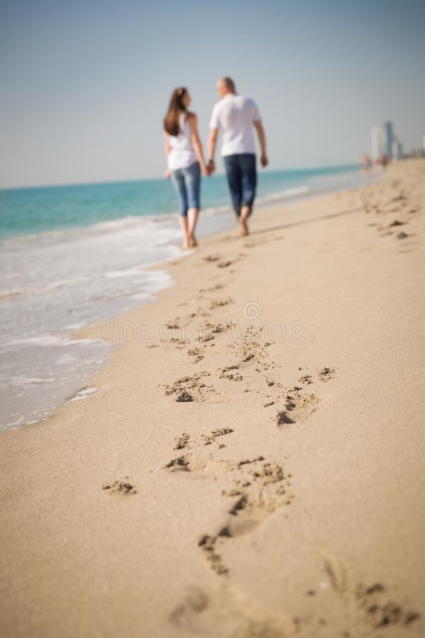 Happy young couple walking on a tropical beach. Lovers in full body length on beach. Back rear view. royalty free stock photo