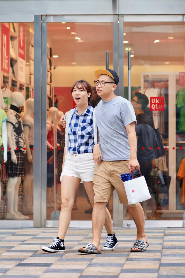 Happy young couple walks out Uniqlo store, Beijing, China stock photo
