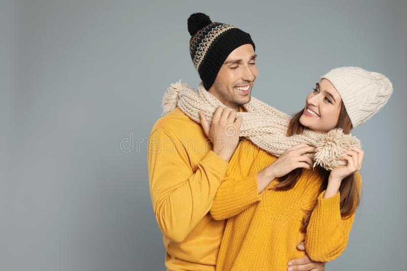 Happy young couple in warm clothes on background, space for text. Winter season. Happy young couple in warm clothes on grey background, space for text. Winter stock photo