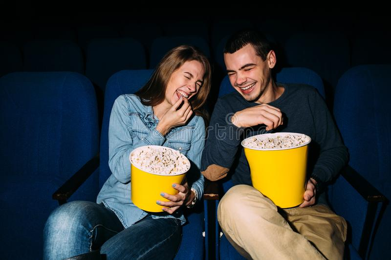 Happy young couple watching comedy movie in cinema, smiling royalty free stock image