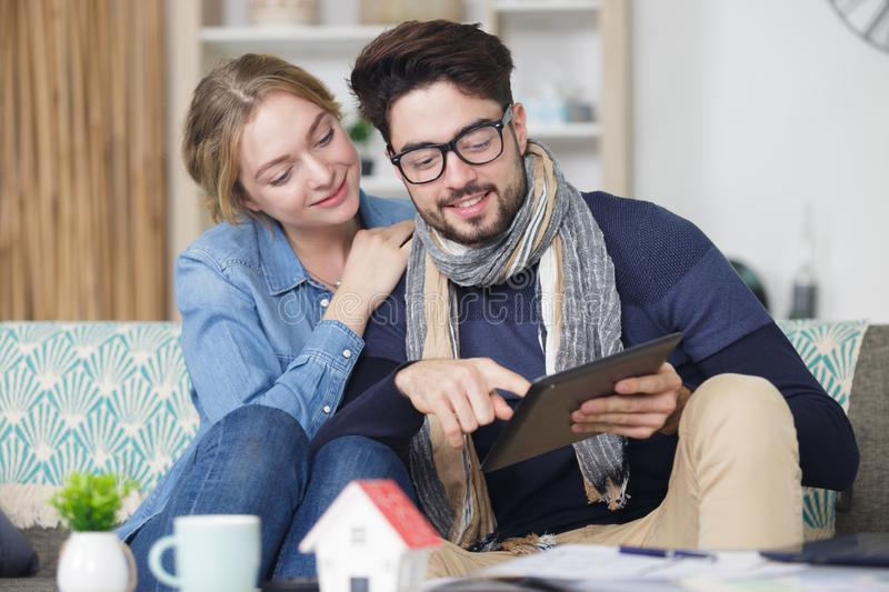Happy young couple watching internet on their tablet stock photo