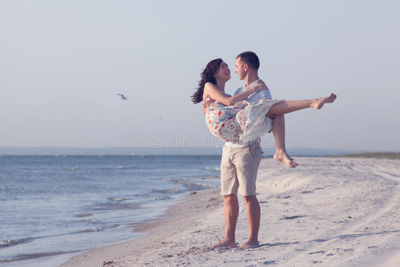 Happy young couple. In white clothing have romantic recreation and fun at beautiful beach on vacations royalty free stock photo