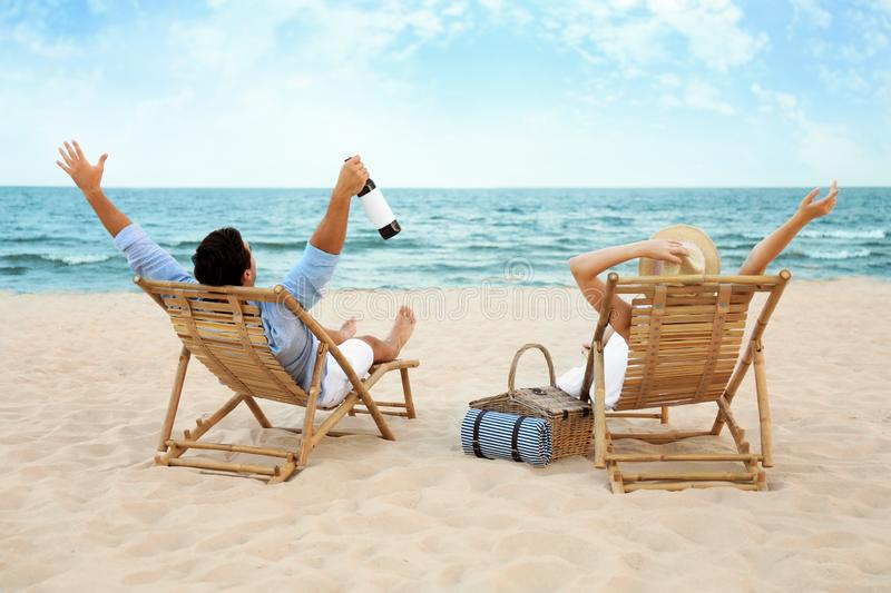 Happy young couple with wine  on deck chairs at  beach stock photo