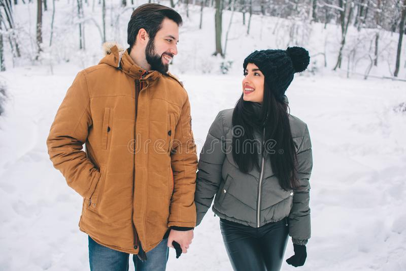Happy Young Couple in Winter . Family Outdoors. man and woman looking upwards and laughing. Love, fun, season and people stock images