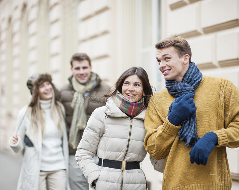 Happy young couples in warm clothing enjoying vacation stock photography