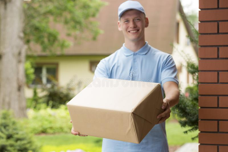 Young courier in blue uniform holding a package. Happy young courier in blue uniform holding a package royalty free stock image