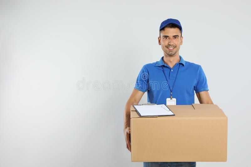 Happy young courier with cardboard box and clipboard on background. Space for text royalty free stock photo