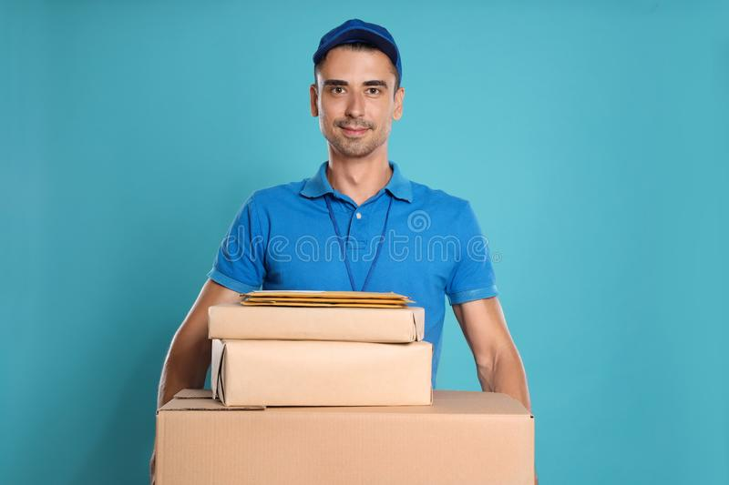 Happy young courier with parcels and envelopes on background royalty free stock photography