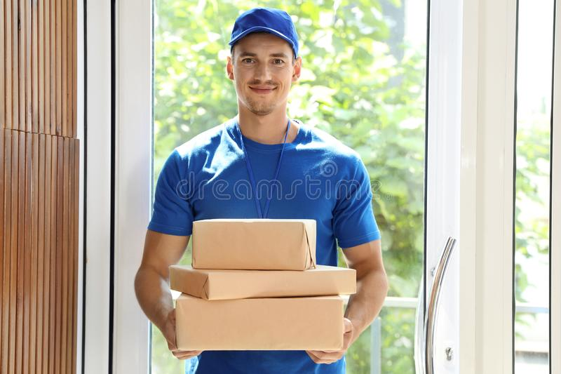 Happy young courier with pile of parcels. In doorway stock images
