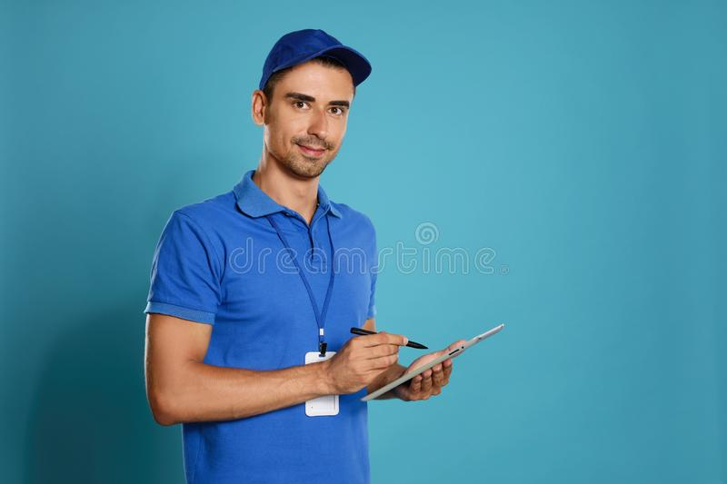 Happy young courier with tablet on background. Space for text stock photos