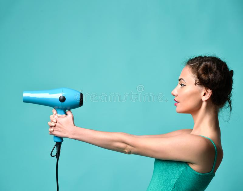 Happy young curly brunette woman with hair dryer on blue mint background royalty free stock photo