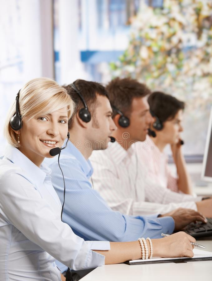 Happy customer service operator. Happy young customer service operator talking via headset, smiling people in background stock photography