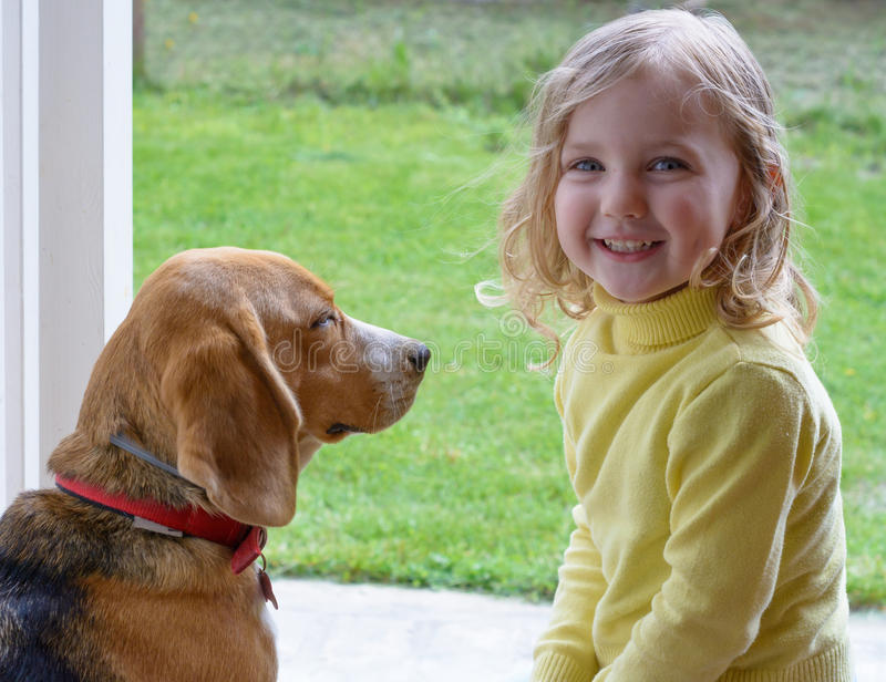 Happy young cute girl with dog playing in garden stock image
