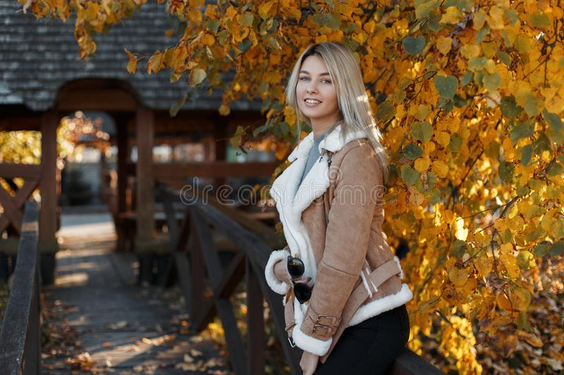 Happy young cute and stylish blonde girl with blue eyes and a sweet smile in oversized warm fashionable clothes walks in the park royalty free stock images
