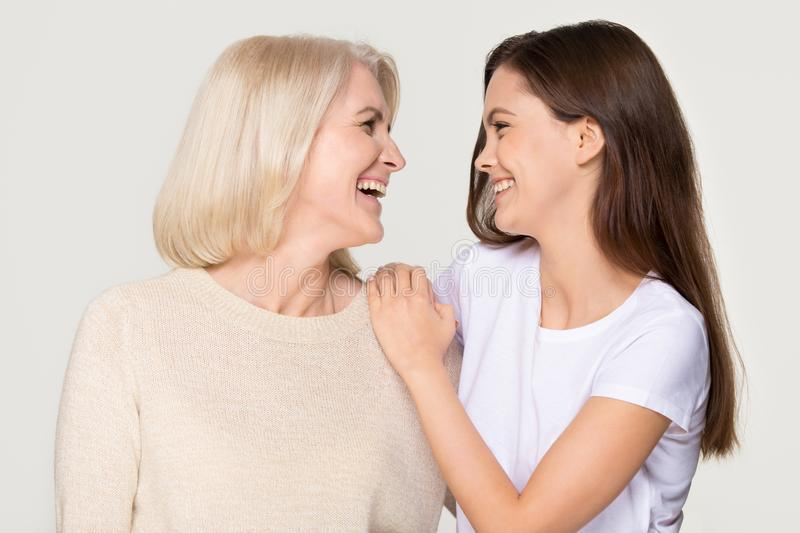 Happy young daughter embracing mature mother laughing isolated on background royalty free stock image