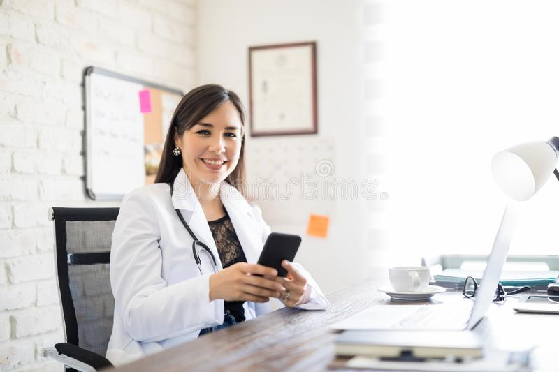 Happy young doctor with phone at office. Portrait of cheerful female doctor sitting at her desk and using mobile phone stock photos