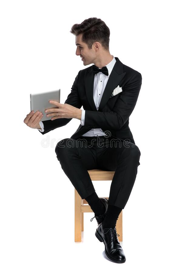 Happy young elegant man holding tab and presenting to side stock photography