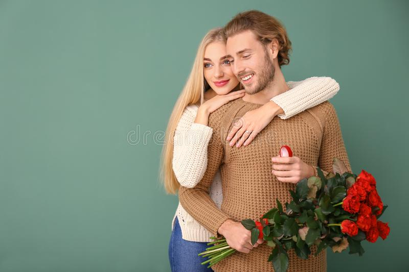 Happy young engaged couple on color background stock images