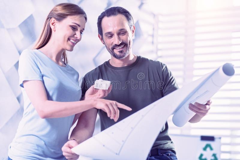 Happy young engineers looking at the graphic and smiling cheerfully stock photo