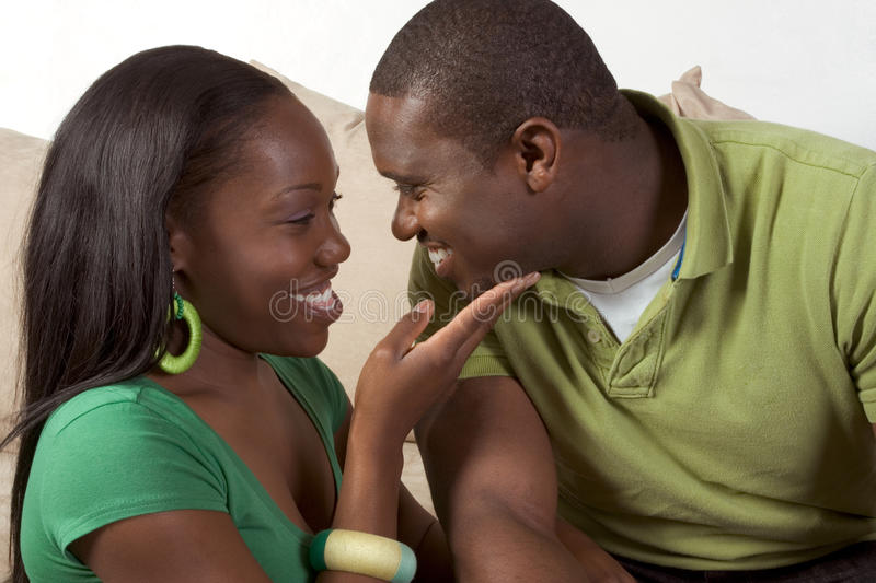 Happy young ethnic black couple sitting on couch stock photography