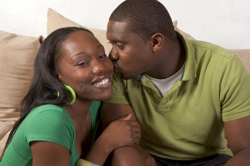 Happy young ethnic black couple sitting on couch stock photos