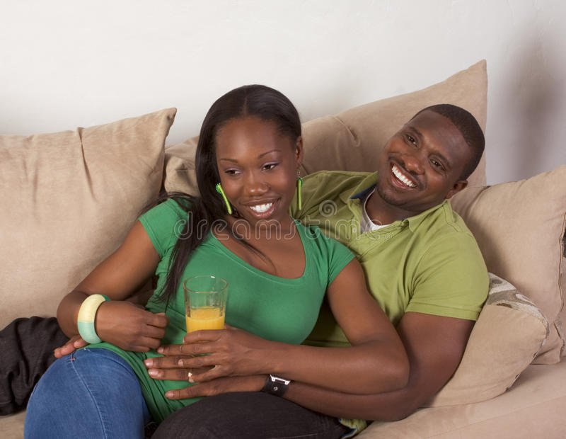 Happy young ethnic black couple sitting on couch. Young African American couple sitting in living room on couch enjoying time together royalty free stock photo