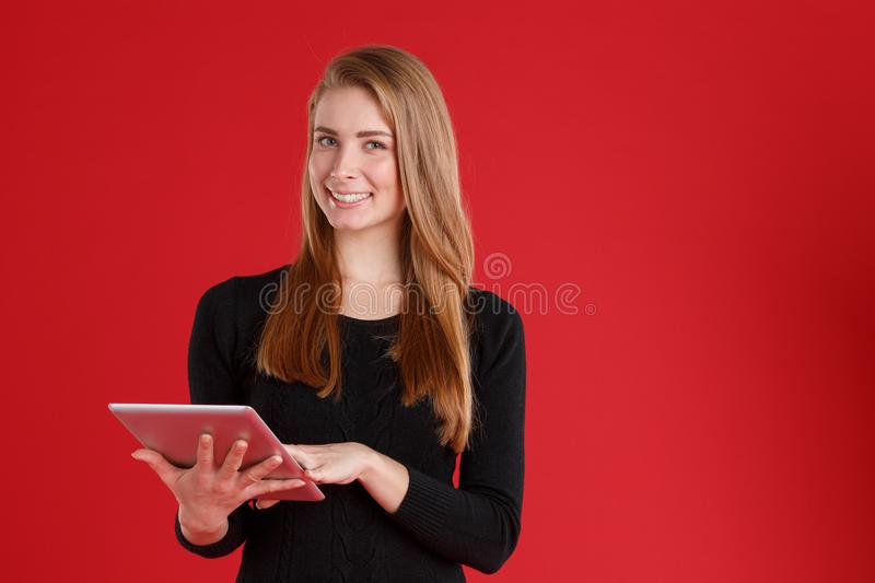 Happy girl holding gray tablet in hand and smiling . On a red background. royalty free stock photography