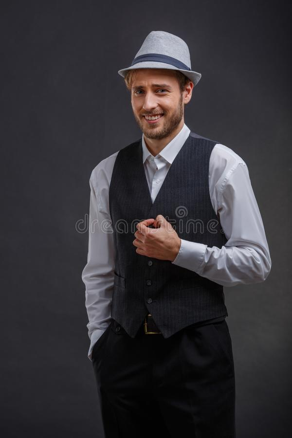 Happy guy in retro suit and hat, smiling wrinkling forehead. Happy young European guy dressed in retro suit with vest and hat, smiling wrinkling forehead. On a royalty free stock photo