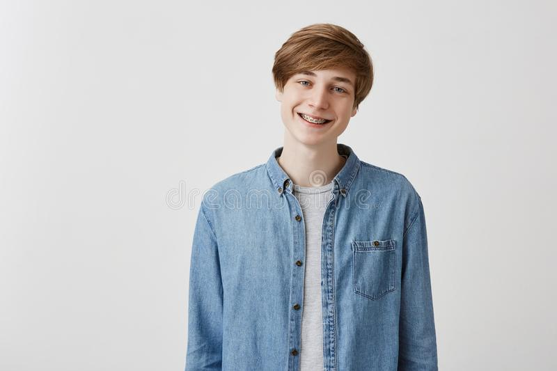 Happy young european man with fair hair and blue eyes, smiles broadly with braces, rejoices to meet friends, has royalty free stock photos