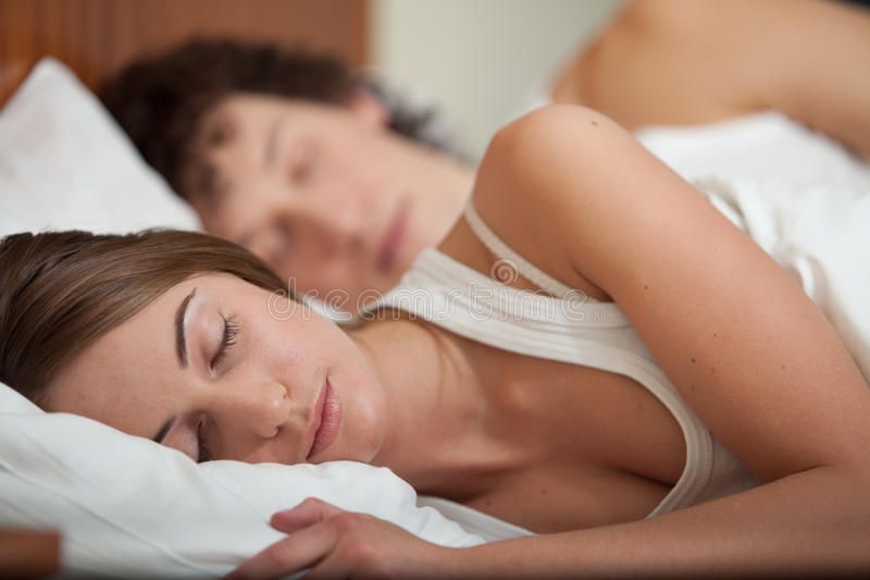 Happy young family. Sleep in the bed at home. Selective focus on woman stock photo