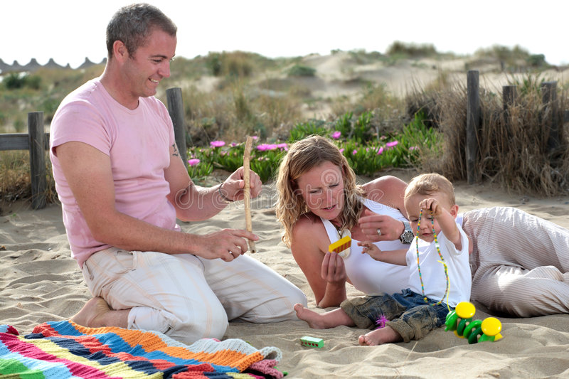 Happy young family. Young family of three playing on the beach (focus on mother royalty free stock photo