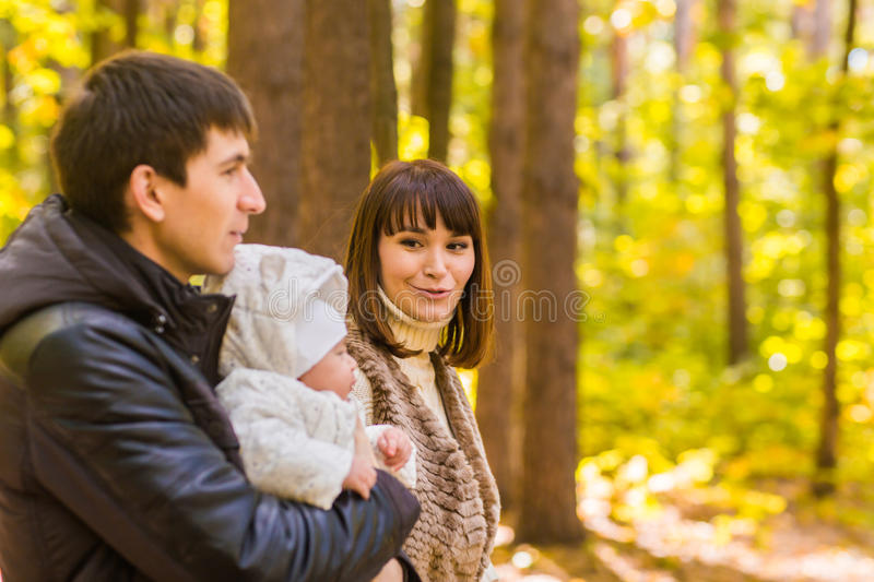 Happy young family in the autumn park outdoors on a sunny day. Mother, father and their little baby boy are walking in royalty free stock photography