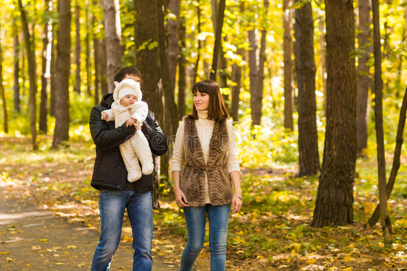 Happy young family in the autumn park outdoors on a sunny day. Mother, father and their little baby boy are walking in royalty free stock images