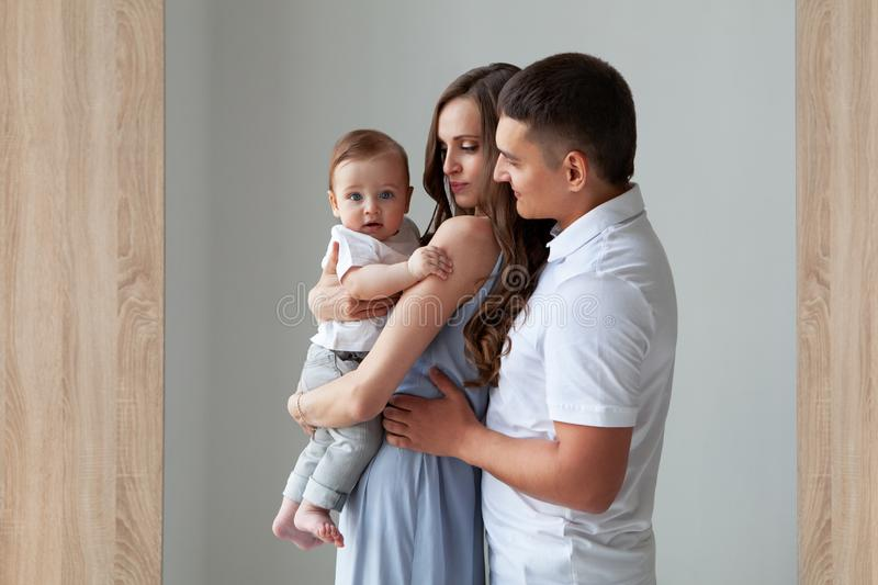 Happy young family. Beautiful Mother and father holding child who looks in camera royalty free stock photography
