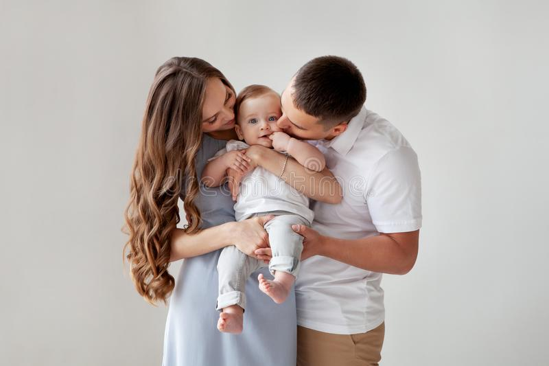 Happy young family. Beautiful Mother and father kissing their baby. Portrait of Mom, dad and smiling child on hands royalty free stock images