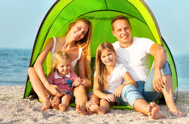 Happy young family camping on the beach royalty free stock photos