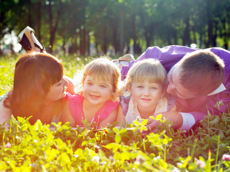 Happy young family with children lying on the grass stock photo