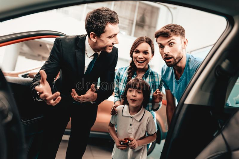 Young Family Are Choosing A New Car In Showroom. Happy Young Family Are Choosing A New Auto In Showroom. Dialogue With Dealer. Cheerful Customer. Look Inside royalty free stock images