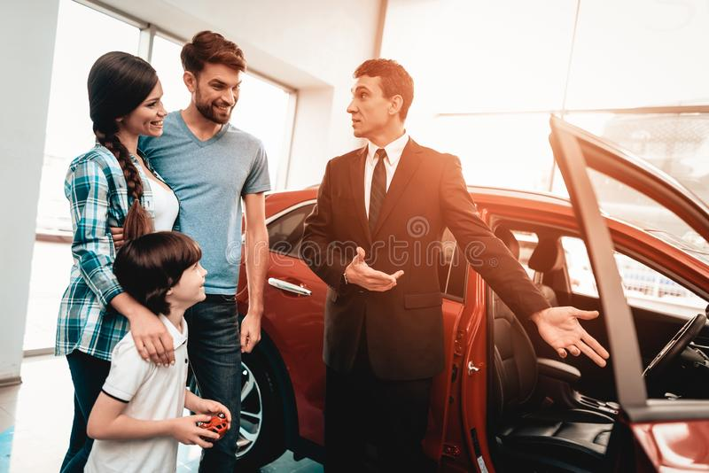 Young Family Are Choosing A New Car In Showroom. Happy Young Family Are Choosing A New Car In Showroom. Dialogue With Dealer. Cheerful Customer. Auto Rewiew royalty free stock photo